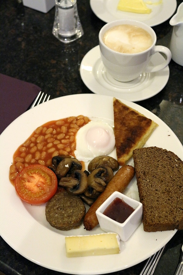 a full Irish breakfast on a plate and a cup of coffee