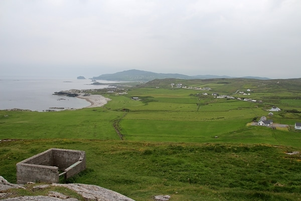 a wide view of green pastures and the sea