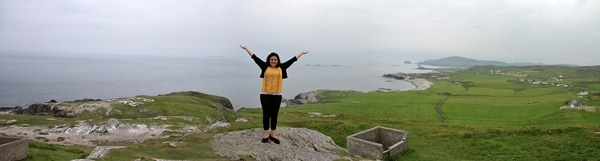 A person standing on a rock at Malin Head overlooking the sea