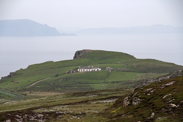 a rocky green hillside with the sea beyond