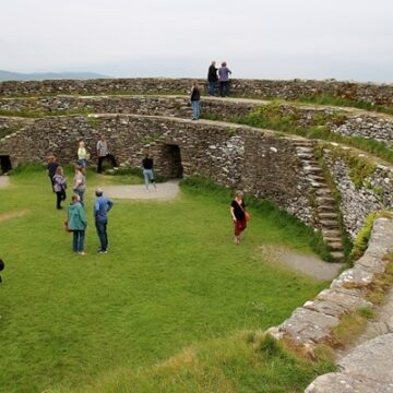 A group of people walking around a stone fort