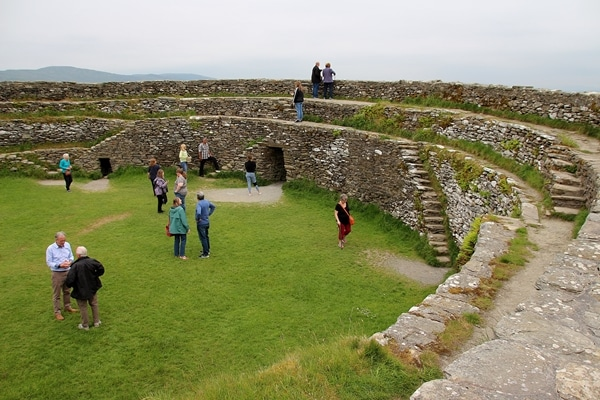 A group of people walking around a large stone fort