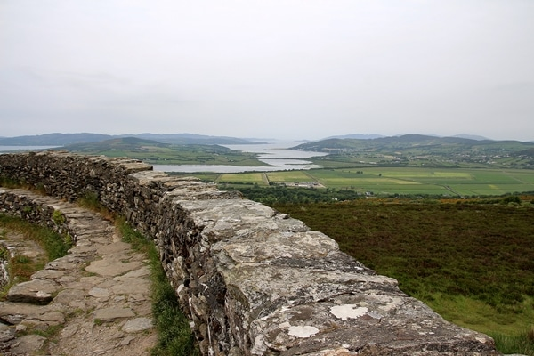 the rocky wall of a fort overlooking green fields