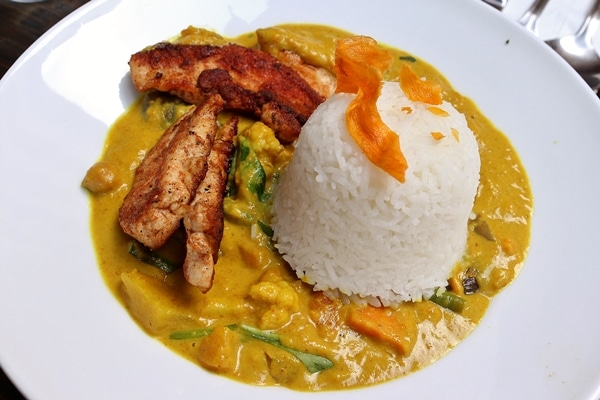 vegetable curry topped with chicken tenders and a scoop of white rice