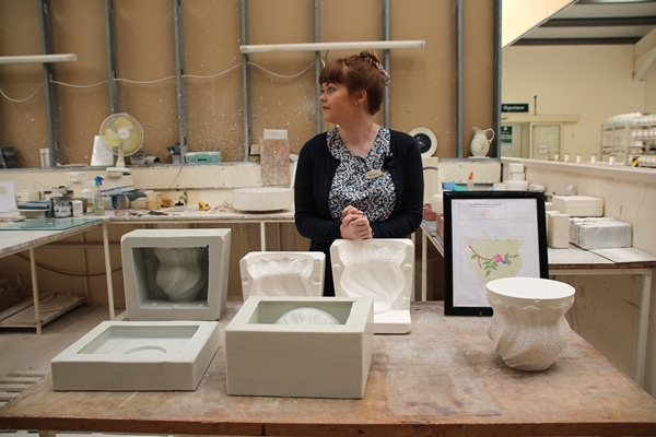a woman behind a pottery display