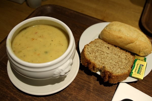a bowl of chowder next to a plate of bread