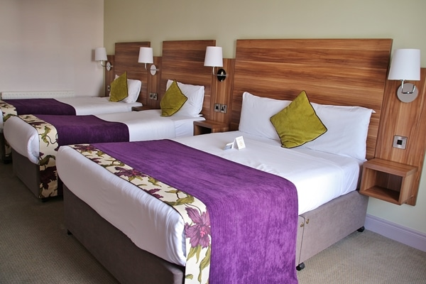 Another angle of a hotel bedroom with 3 beds