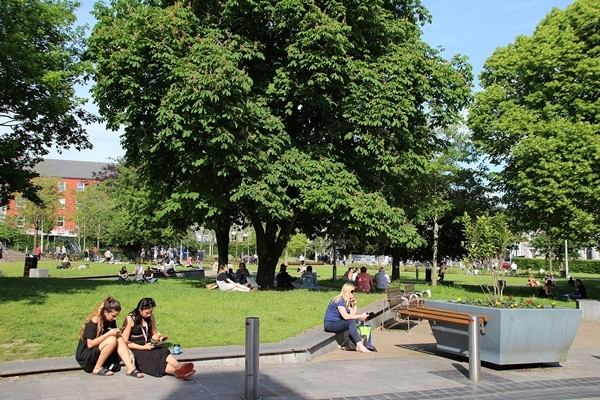 A group of people sitting on a bench in a park