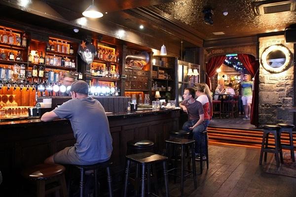 A group of people sitting inside an Irish pub