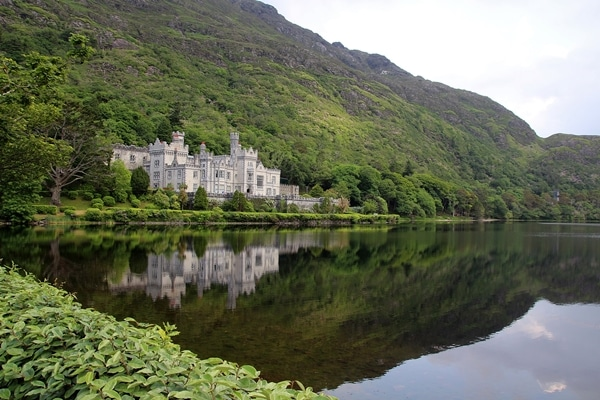 Kylemore Abbey reflected in a pond, surrounded by mountains