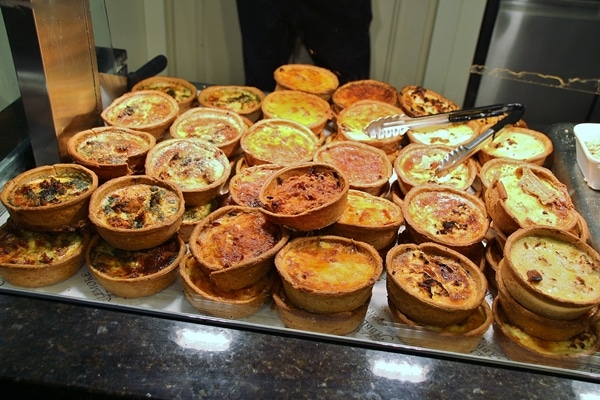 A glass display case featuring individual quiches