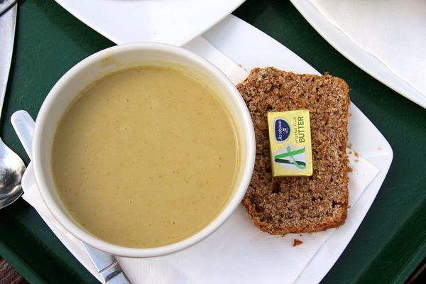 a cup of soup with brown bread on the side