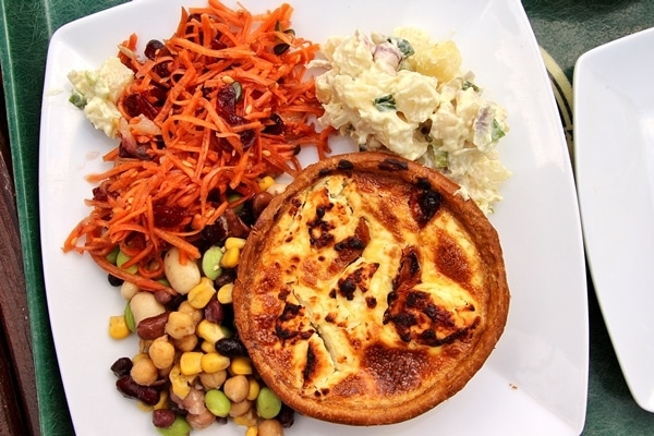 a small quiche on a plate with a variety of salads on the side