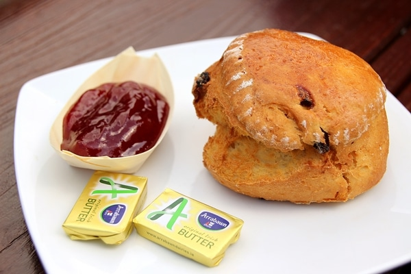 a scone with a side of butter and jam