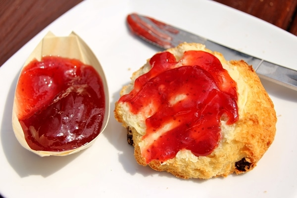 half a scone topped with butter and jam