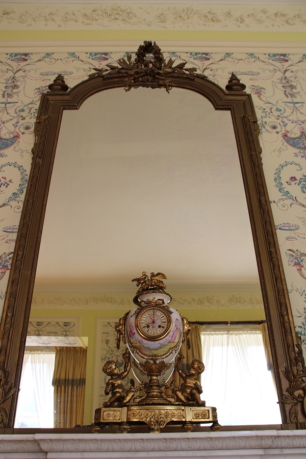 a mirror with an ornate clock in front of it