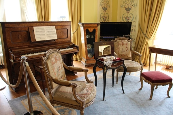 A living room filled with ornate chairs and a piano