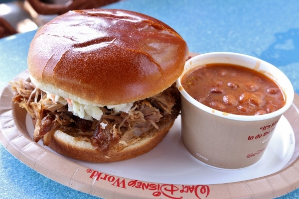 a pulled pork sandwich with a side of baked beans