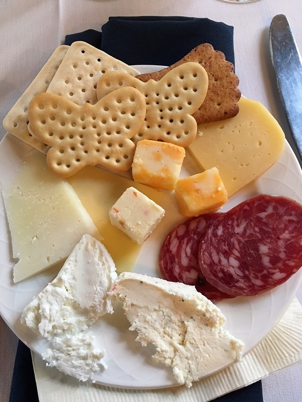 A plate of cheese, crackers, and cured meat