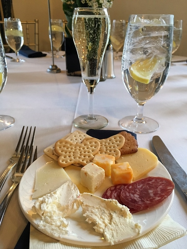 a cheese plate and a glass of sparkling wine