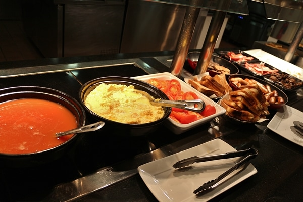 various hot breakfast foods on a buffet