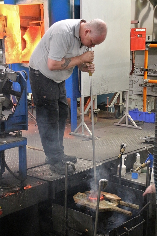 A man blowing glass in a cast iron mold