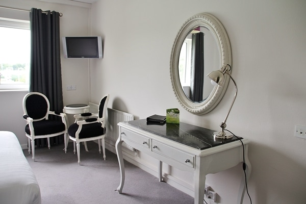 a desk and mirror in a hotel room