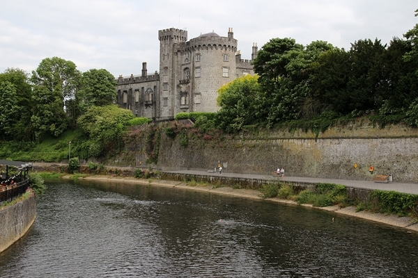 view of Kilkenny Castle from a bridge over a river