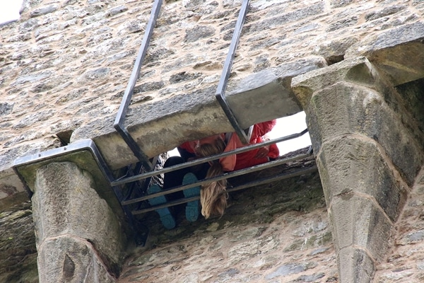 view from below of a person kissing the Blarney Stone