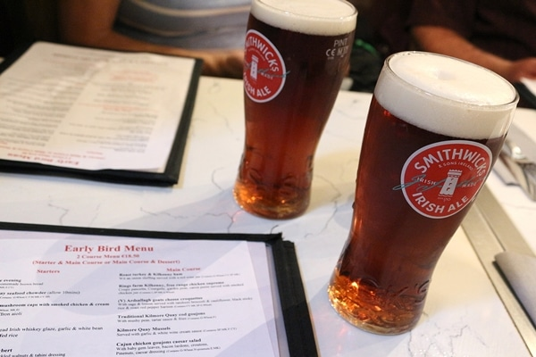 2 glasses of Irish ale on a table with restaurant menus