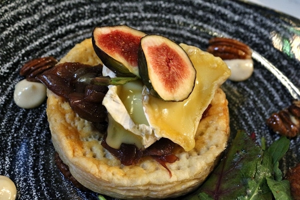 closeup of a tart topped with cheese and figs