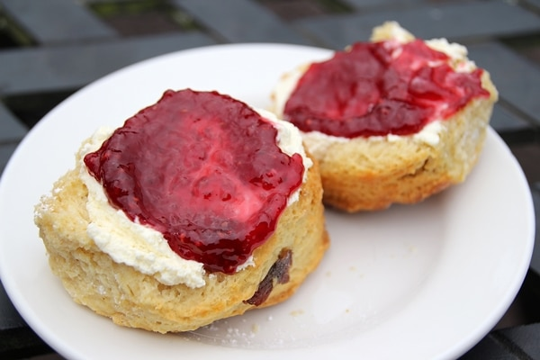 a halved scone topped with clotted cream and jam