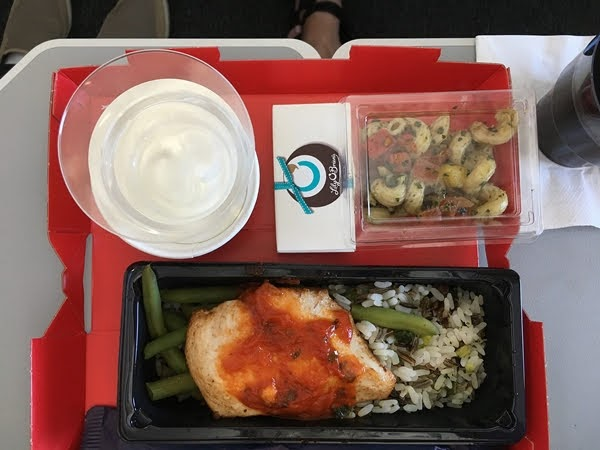 A tray of food on an airplane tray table