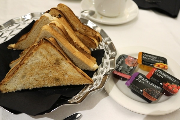 toast on a platter with small packages of jam on the side