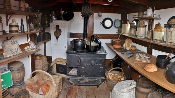 An old kitchen on a ship with a pot and wooden counters