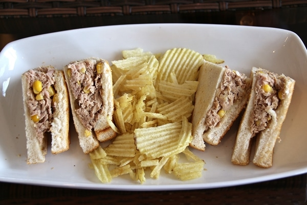 a tuna sandwich cut into quarters on a plate with potato chips