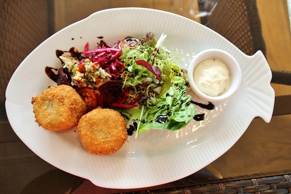 fish cakes on a plate with salads