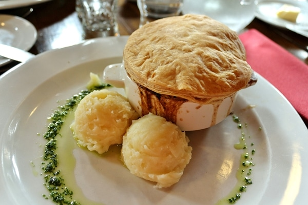 a pot pie with scoops of mashed potatoes on the side
