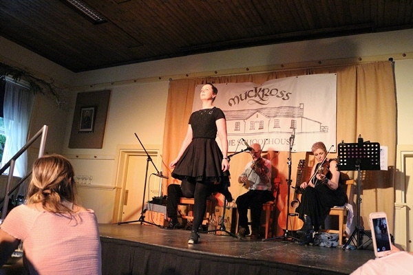 a woman dancing on a stage in front of a band