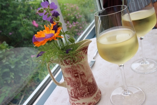 A glass of wine next to a pitcher of flowers