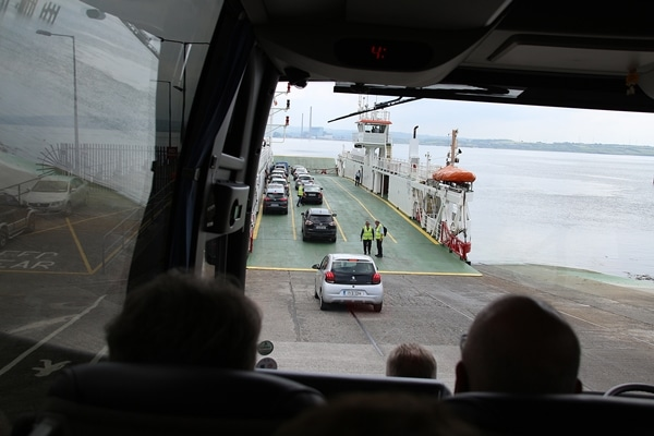 view of cars driving onto a ferry