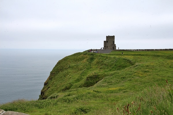 a stone building on top of a grassy hill by the sea