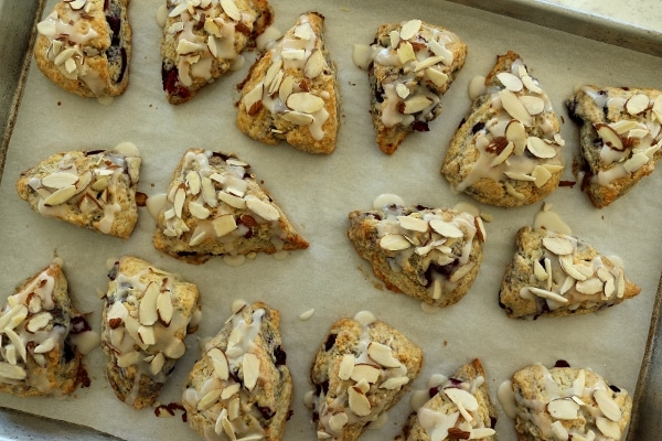 scones topped with almonds on a baking sheet