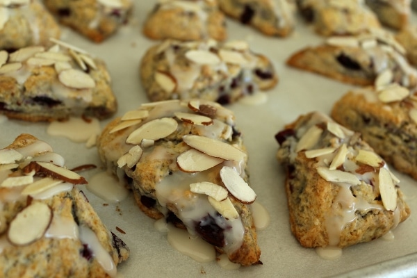 a baking sheet of scones topped with sliced almonds