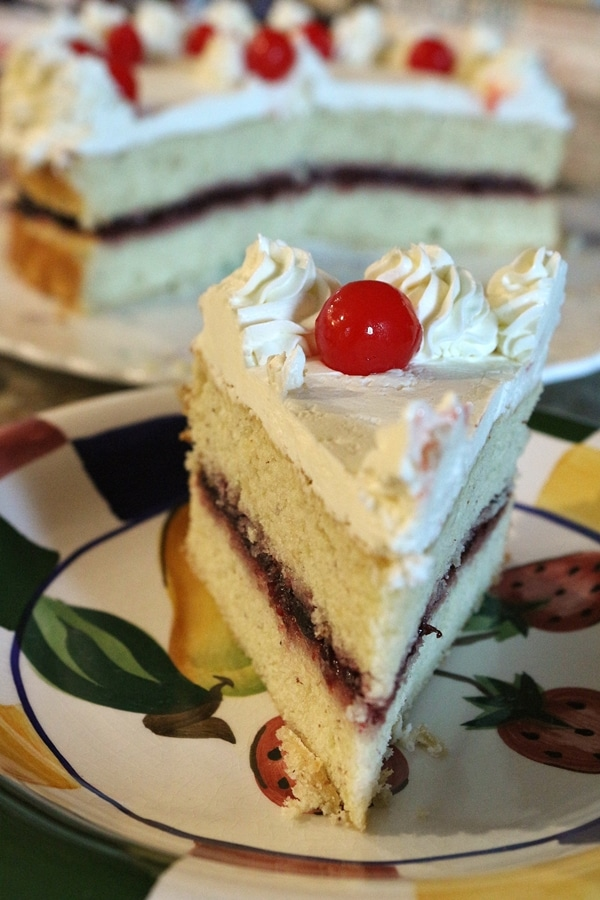 A piece of cake with cherry filling on a plate