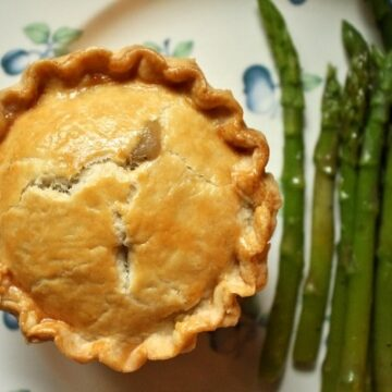 Individual chicken and mushroom pie served on a plate with asparagus