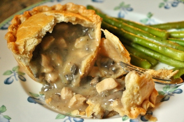 An individual chicken and mushroom pie broken open with the filling spilling out