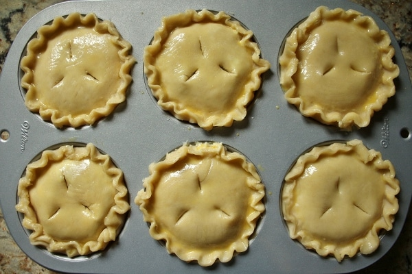 6 small pies assembled in a jumbo muffin pan, brushed with egg wash
