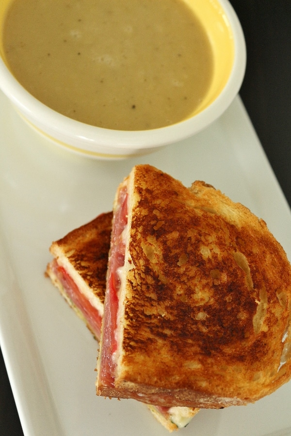 Overhead view of a grilled cheese with salami, tomato, and pesto on a white plate with a cup of soup in a white and yellow striped bowl.