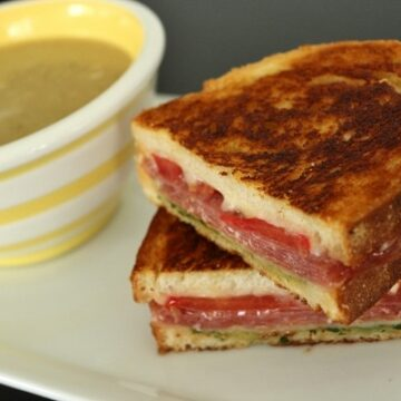 Cross section of an Italian grilled cheese sandwich with a cup of soup